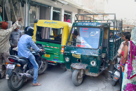 India, Jaisalmer - March 5, 2018: narrow streets and active traffic of cargo rickshaws and motorcycles. to pass a pedestrian it is very difficult