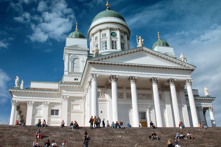 Helsinki , Finland - August 20, 2017: Famous landmark in Finnish capital. Senate Square with Lutheran cathedral, tourists sit on steps Редакционное