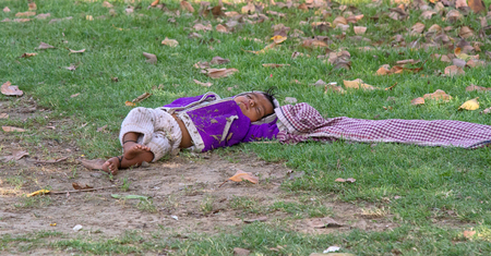 India, new Delhi - March 26, 2018: child sleeps on the grass. left unattended by the mother, the child sleeps on the ground.