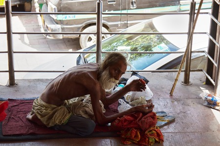 India, new Delhi - March 27, 2018: skinny Indian man tramp spread a blanket in the business center at the entrance. this is his place of residence.