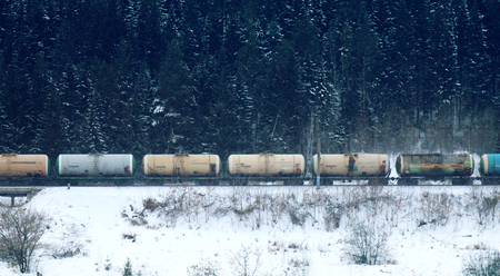 freight train moving through coniferous forest during snowfall along frozen river among hills. Northern country. Side fron top Stock Photo