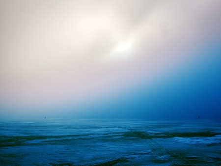 The frozen winter North sea ice and ice road, muddy sun (sea fog) that breaks through dark clouds. Wintry somber landscape
