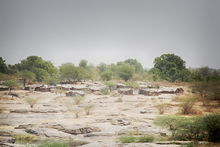 The poor village consists of a group of Adobe huts among scrub and rocky soil. India Stock Photo