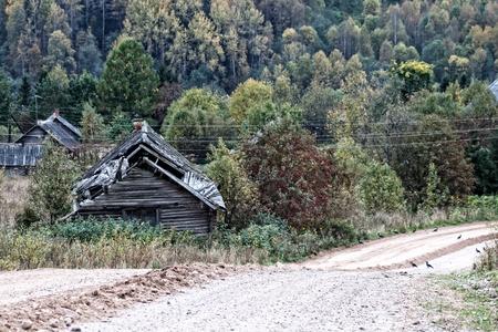 Le vieux village russe à la lisière de la forêt est détruit. Nord-ouest de la Russie. Automne, route de gravier au premier plan
