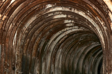 An old tunnel with an arched metal beams in mauntain