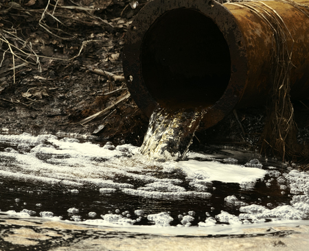 Dirty water flows out of the old rusty pipe without cleaning. Pollution of natural water bodies Stockfoto