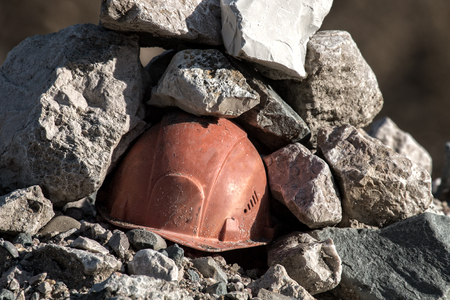 Working helmet on a pile of stones. The incident in the mining industry or the accident happened Stock Photo