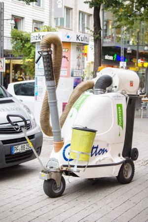 Karlsruhe, Germany - September 13, 2017: street cleaner in cleaning sidewalks, cleaning works, work of modern janitor