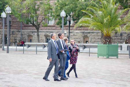 Metz, France - September 20, 2017: Businessmen foreigners (the delegation leaders, business-partner) walking through the streets accompanied by a woman guide (Secretary, assistant)