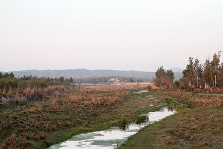 River during winter low water in tropical area. You can see indigenous shores (bedrock coast), riverbed and level in flood. Flocks of white herons wintering in Indian subcontinent