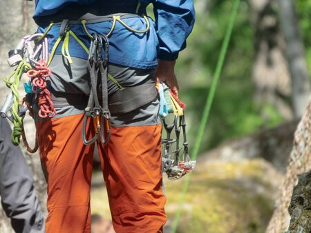 Climber partner insures. Quickdraw, carabiner hanging on a safety system. Active extreme rest in summer for weekend Фото со стока