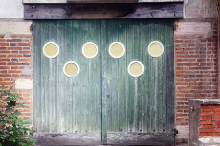 Wooden gates of the old town house on the outskirts with round decorations. Dijon