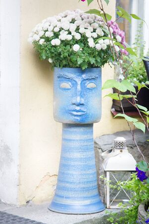 Street vase with flowers in the form of a female mask in Tallinn and decorative old lantern Archivio Fotografico