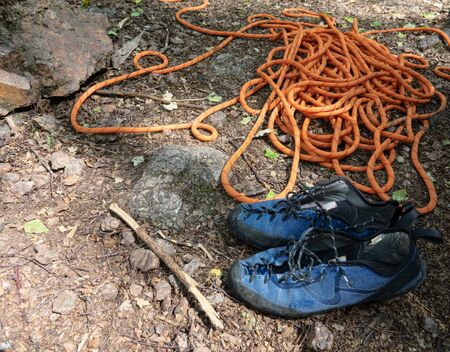 Rope and climbing shoes are waiting for sportsman. Active extreme rest in summer for weekend Фото со стока