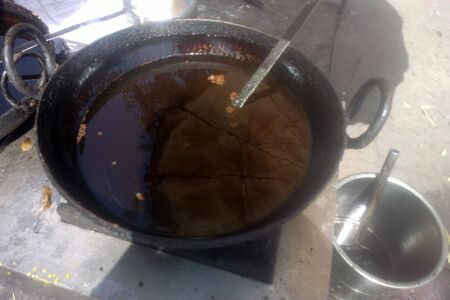 Hot vegetable oil in a deep frying pan for frying donuts. Indian kitchen utensils and gastronomic tourism
