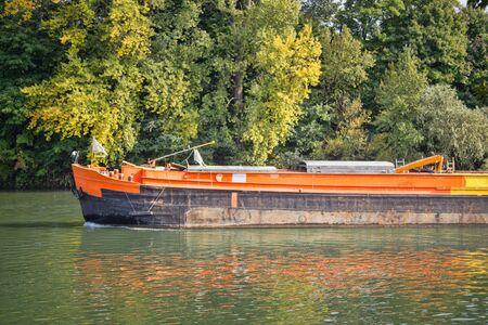 River navigation in France. Barge on Seine. cargo ships floating along riverside river shipping traffic service ship, vessel of inland navigation