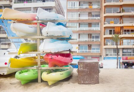 Canoes and boats are stacked for storage for the winter on the Mediterranean coast near houses. Canoeing is possible right from the door of the house. Spain