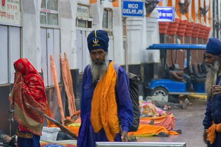 India, Delhi - March 19, 2018: Indian Sikhs as railway passengers in traditional blue clothes: lungi, broad pants, shirts, vests, turban (pagri), symbolic spear (nihang warriors), do't cut hair