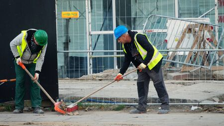 Warsaw, Poland - October 15, 2019: Cleaning debris workers in helmets on construction site