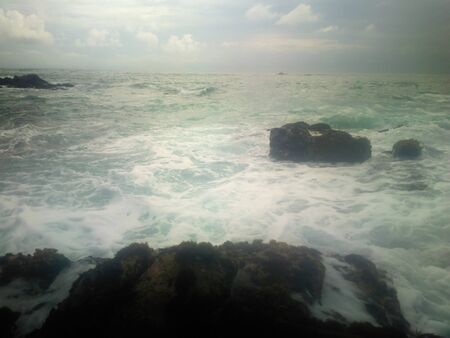 Dark cliffs on coast of Indian ocean and storm surges in haze. Powerful waves very close