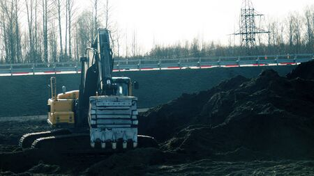 Construction of the highway. The work of earthmoving equipment. Excavator in the process of leveling the slope of the road and the ditch, side piling