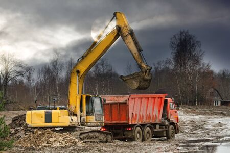 Preparation of the site for construction, leveling the soil. Excavator loads excess soil into dump trucks. Autumn construction, cloudy sunlight, North