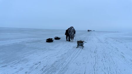 Gloomy winter morning over the frozen pond, frozen sea. Fishermen go ice fishing and drag fishing equipment on a sled
