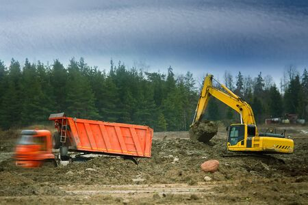 Preparation of the site for construction, leveling the soil. Excavator loads excess soil into blurred dump trucks