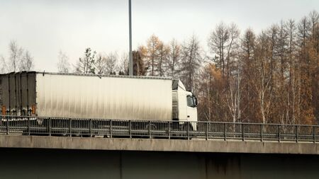 Unrecognizable truck transport on road. Transport overpasses on the highway for the transport of orders and goods