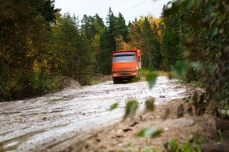 The dump truck moves on a muddy road and splashes liquid mud, all-terrain vehicle. Autumn forest around. Car partly blur to not identify the manufacturer company