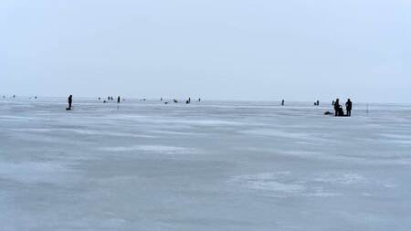 Winter fishing on the sea. Silhouettes of fishermen in kilometers from the shore