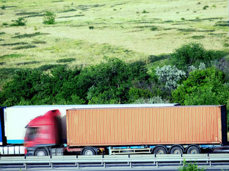 Blurred unrecognizable truck transport on road. Transport overpasses on the highway for the transport of orders and goods