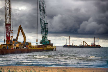 Construction of offshore section of gas pipeline on bottom of Baltic sea Nord stream-2. Pier goes into Nara Bay, excavator aligns bottom under bed of gas pipeline. Auxiliary vessels at sea