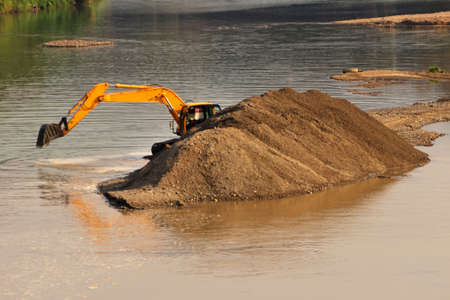 Excavator extracts sand and pebbles from a river in Southeast Asia. Construction and road work on ground