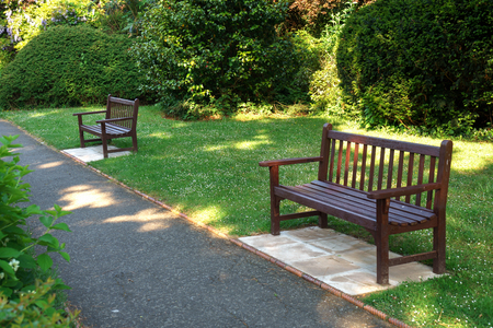 Stylish bench in English summer garden park.