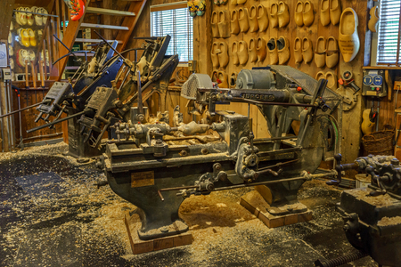 traditional old clog making machine in workshop with wooden shoes on display Banco de Imagens
