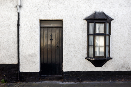 Exterior View of a Beautiful Old English Stone Cottage with door and window 写真素材