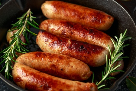 Freshly cooked butchers made, homemade sausages with rosemary in cast iron frying pan