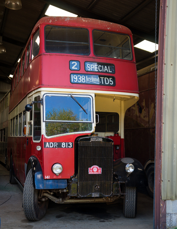 Vintage Red double-decker bus in garage ready for annual Devon coastal run, Winkleigh, United Kingdom, August 5, 2018