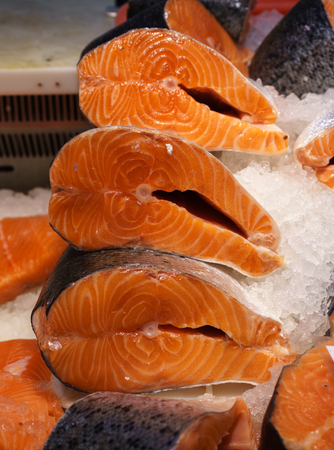 Fresh salmon steak for sale in the ice. Red fish. Showcase of a fish store.