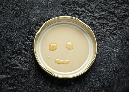 face smile made with honey drops on lid