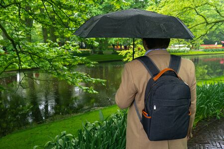 man is standing under umbrella in rainy spring day in park.