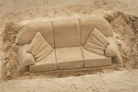 Sand sculpture of a sofa, couch, settee and cushions carved out of golden beach sand.