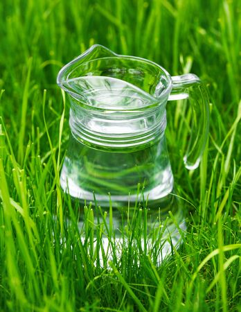 A glass jar of water surrounded by green grass, healthy concept