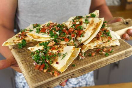 man serving Mexican chicken quesadillas on wooden board