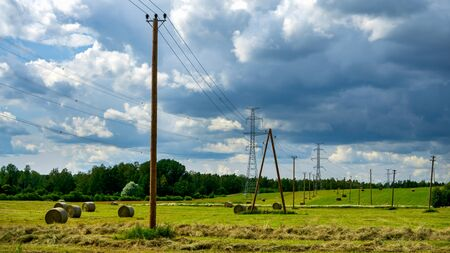 Countryside Landscape with straw hay bales on agricultural field, blue sky and power lines