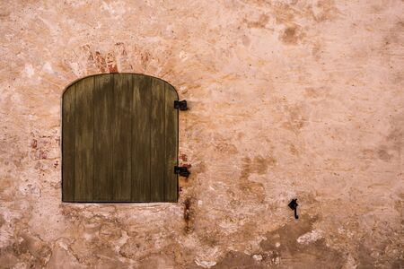 old arched Window closed by wooden shutters and red wall Banco de Imagens