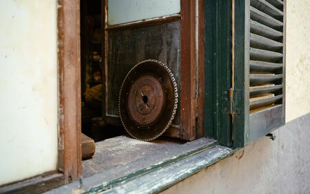 old, vintage circular saw ring for cutting wood on window sill in workshop.