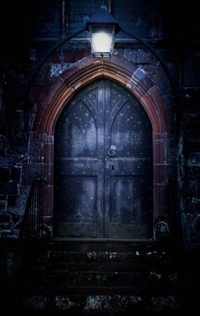 Close-up of mystical medieval wood entrance doorway portal in parallel worlds with ancient brick arc and glowing in the dark lantern