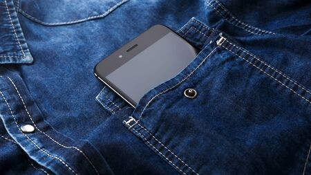 smartphone mobile in Blue jeans shirt pocket with black screen